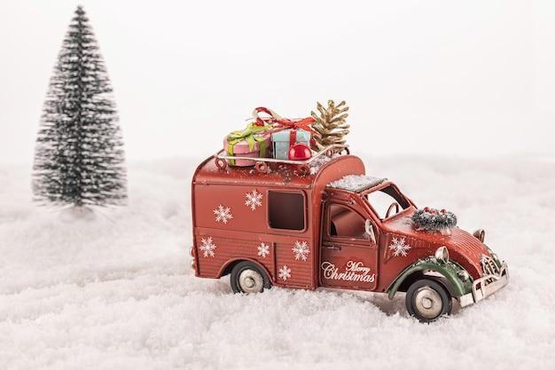 Petite Voiture Jouet Décorée D'ornements Sur La Neige Artificielle Avec Un Arbre De Noël En Arrière-plan Photo gratuit