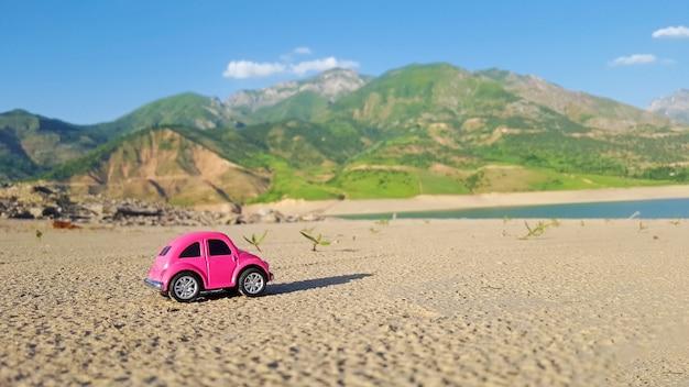 Petite voiture de jouet rose sur fond de nature. vacances d'été, concept de voyage. Photo Premium