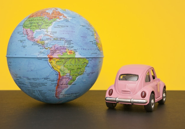 Petite Voiture Rétro Rose Avec Sphère Globe Terrestre. Photo Premium