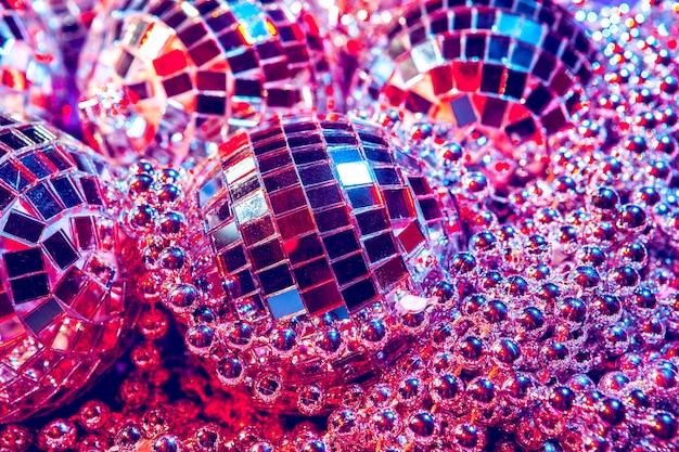 Petites boules disco brillantes étincelantes dans une belle lumière pourpre. concept soirée disco Photo Premium