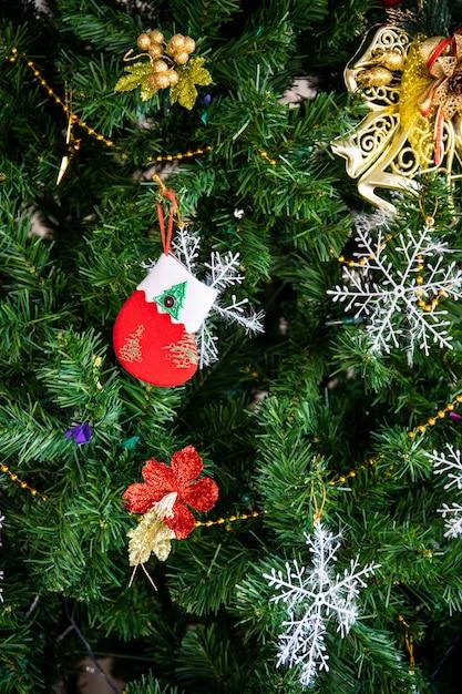 Petites Chaussettes Rouges De Père Noël Décorées Sur L'arbre De Noël. L'arbre De Noël Et Les Boîtes De Cadeaux De Noël Préparés Dans La Salle Pour La Célébration Du Festival De Noël Et Du Nouvel An. Mur Thème Festival Photo Premium
