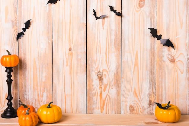 Petites citrouilles et chauves-souris près du mur Photo gratuit
