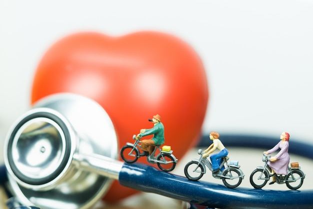 Petites figures à cheval sur le stéthoscope et le coeur rouge avec fond blanc. Photo Premium