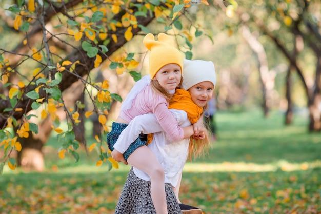 Petites filles adorables au chaud jour en automne parc en plein air Photo Premium