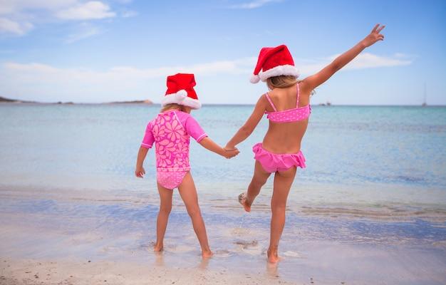 Petites filles adorables en chapeaux santa pendant les vacances à la plage Photo Premium