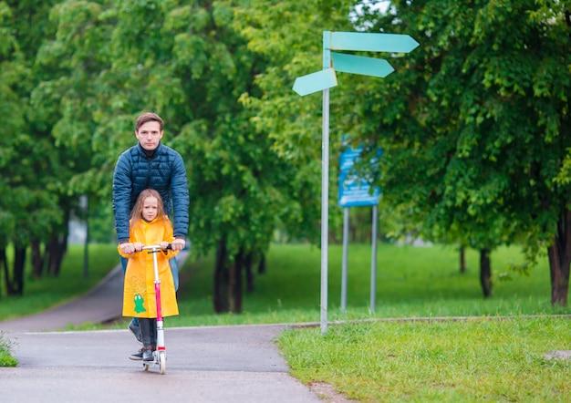 Petites filles adorables sur des scooters avec papa en automne parc en plein air Photo Premium
