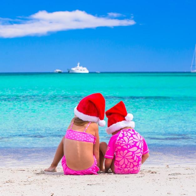 Petites filles en chapeaux santa pendant les vacances d'été Photo Premium