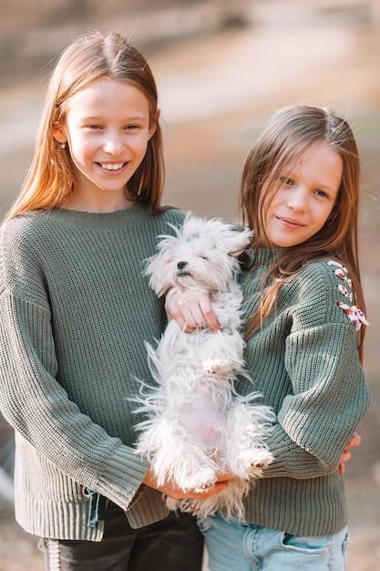 Petites filles avec un chiot blanc. un chiot dans les mains d'une fille Photo Premium