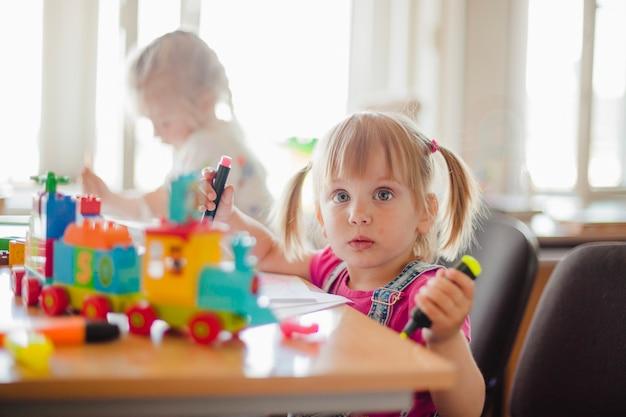 Petites filles dessinées dans la salle de jeux Photo gratuit