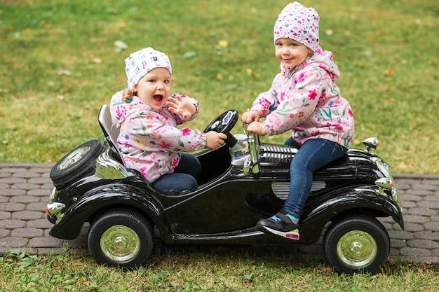 Les Petites Filles Jouant Avec Une Voiture Photo gratuit