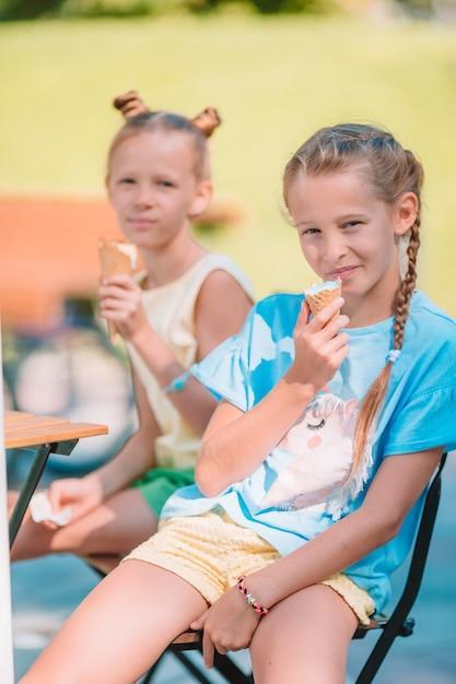 Petites Filles Mangeant Des Glaces En Plein Air En été Au Café En Plein Air Photo Premium