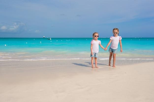 Petites filles mignonnes profiter de leurs vacances d'été sur la plage Photo Premium