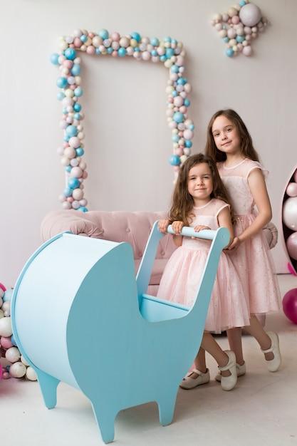 Les Petites Filles En Robes Roses Jouent Avec Une Poussette Bleue Comme Des Petites Mamans Photo Premium