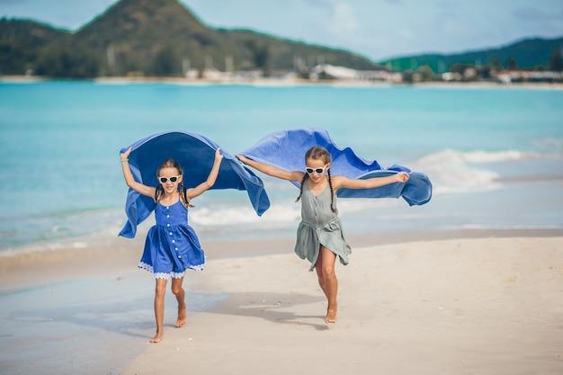 Petites filles s'amusent avec une serviette de plage pendant des vacances tropicales Photo Premium