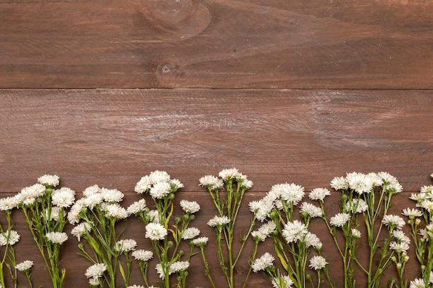 Petites fleurs blanches sur fond en bois Photo gratuit