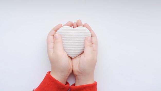 Petites Mains De Filles Tiennent Coeur Beige Rayé De Tissu Sur Fond Gris. Photo De Haute Qualité Photo Premium