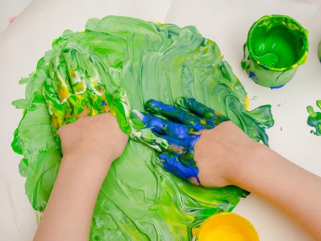Petites mains jouant avec de la peinture. Photo Premium