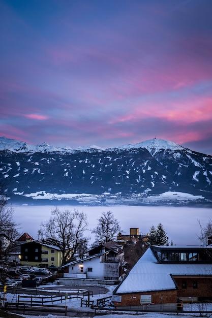 Petites Maisons Enneigées Dans Une Ville Avec Un Ciel Et Des Montagnes Incroyables Photo gratuit