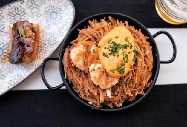 Petites nouilles de printemps aux grosses crevettes et sauce au piquillo Photo Premium
