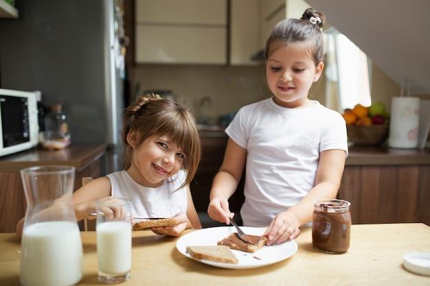 Petites sœurs prenant le petit déjeuner le matin Photo gratuit