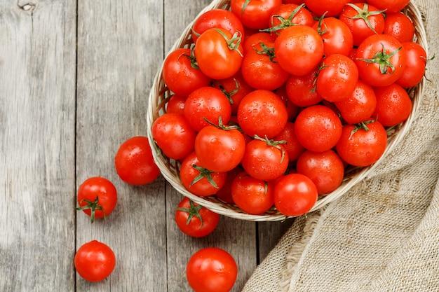 Petites tomates rouges dans un panier en osier sur une vieille table en bois. cerise mûre et juteuse Photo Premium