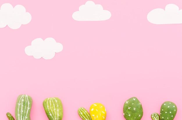 Petits cactus avec des nuages de papier sur la table Photo gratuit