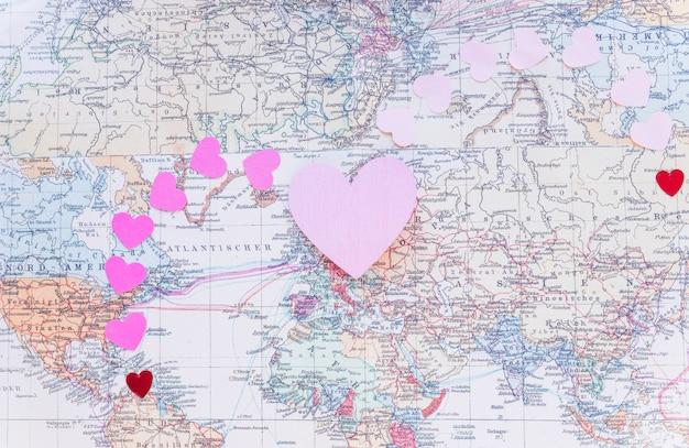 Petits coeurs de papier colorés sur la carte du monde Photo gratuit