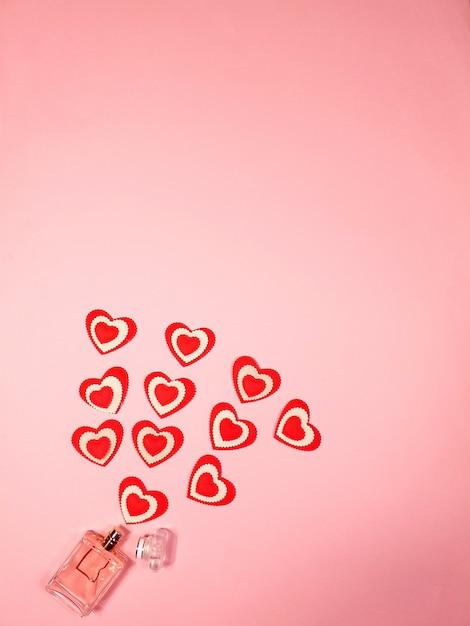 Petits Coeurs Rouges Et Une Bouteille De Parfum Sur Une Rose Photo Premium