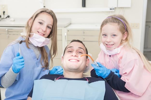 Petits dentistes examinant la bouche d'un patient adulte Photo Premium