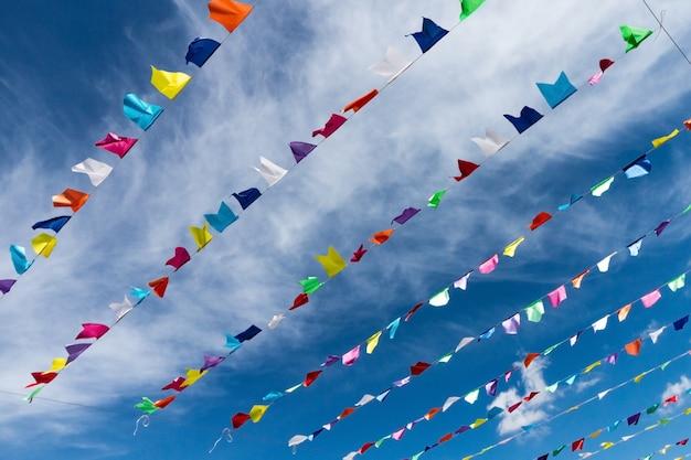 Petits Drapeaux Colorés Mignons Sur La Corde Suspendue à L'extérieur Pour Des Vacances Avec Le Ciel Bleu Brillant Fond De Nuages blancs. Italie, Sardaigne. Photo gratuit