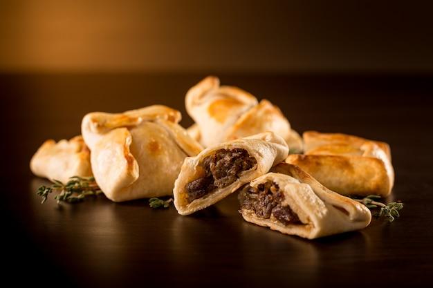 Petits empanadas à la viande dans une ambiance sombre Photo Premium