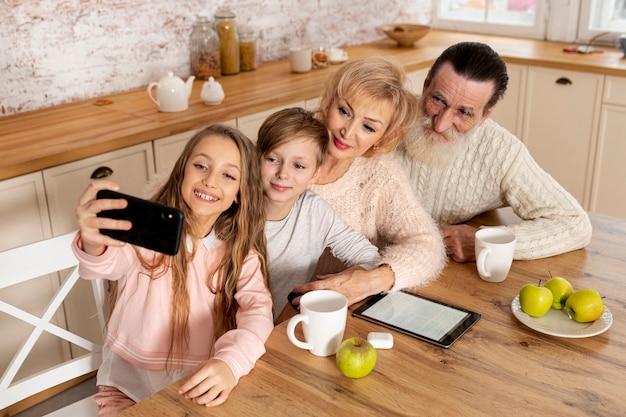 Petits-enfants à Angle élevé Prenant Un Selfie Avec Leurs Grands-parents Photo gratuit