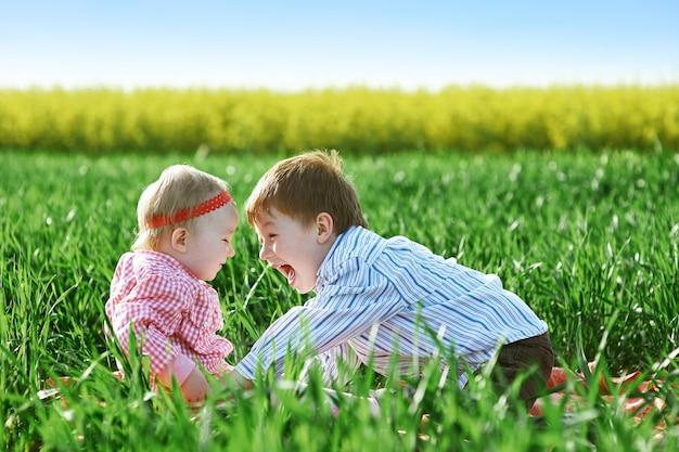 Petits enfants garçon et fille jouent sur l'herbe verte Photo Premium
