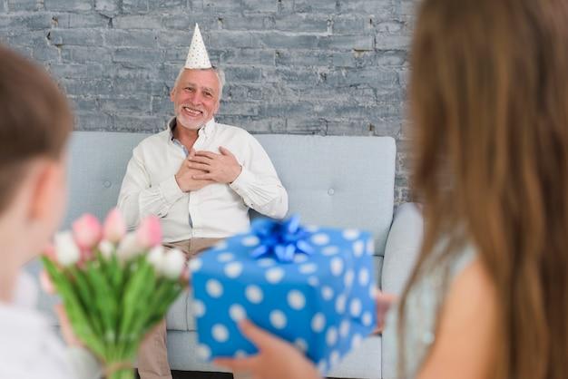 Petits-enfants montrant des cadeaux à leur grand-père surpris Photo gratuit