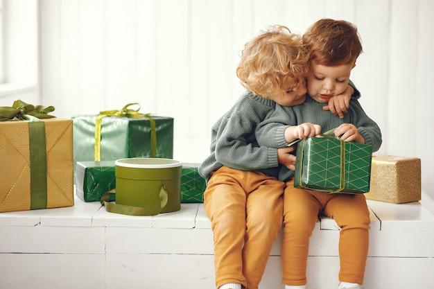 Petits Enfants Près De Sapin De Noël Dans Un Pull Gris Photo gratuit