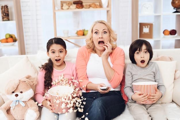 Petits-enfants regardent un film effrayant avec grand-mère Photo Premium