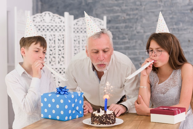 Petits-enfants soufflant des cornes de fête avec leur grand-père soufflant de sparkler sur un gâteau d'anniversaire Photo gratuit