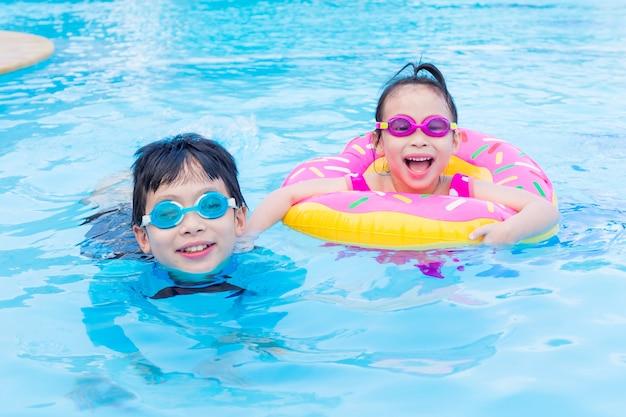 Petits frères et sœurs asiatiques heureux ensemble dans la piscine Photo Premium