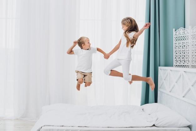 Petits frères et soeurs sautant au lit Photo gratuit
