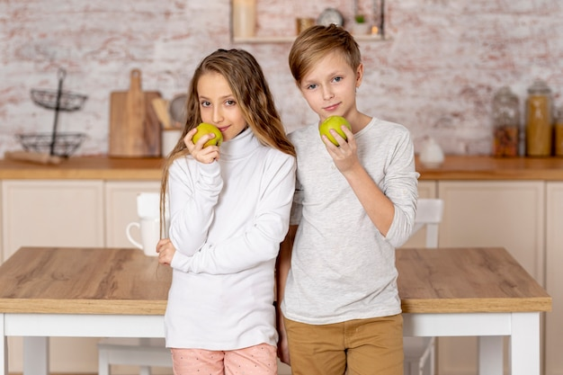 Petits Frères Et Sœurs Tenant Une Pomme Photo gratuit