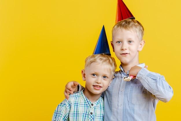 Les Petits Garçons Mignons De Frères En Chapeau D'anniversaire S'embrassent Sur Le Jaune. Photo Premium
