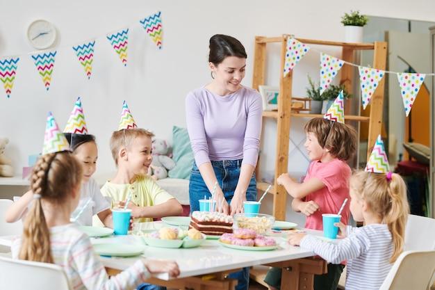 Un Des Petits Garçons Mignons Racontant Une Blague à Ses Amis Et Heureuse Jeune Femme Assise Par Table De Fête à La Maison D'anniversaire Photo Premium