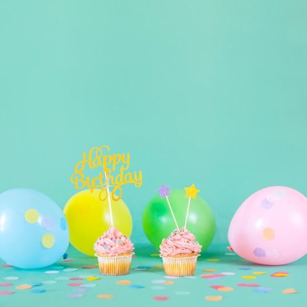 Petits gâteaux d'anniversaire roses avec des ballons Photo gratuit