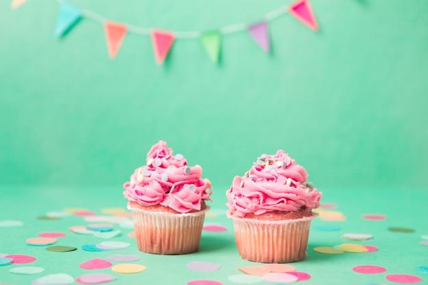 Petits gâteaux d'anniversaire roses avec guirlande Photo gratuit