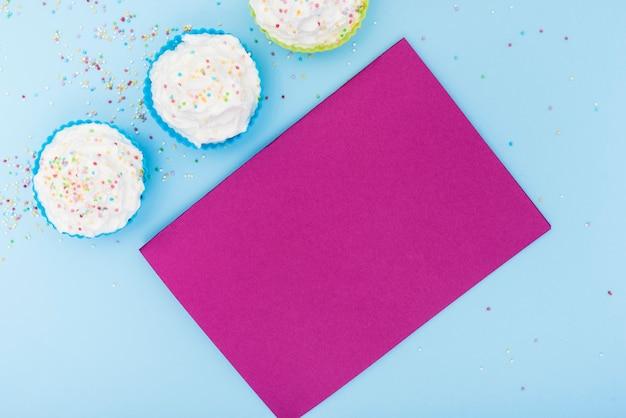 Petits gâteaux colorés avec une carte rose vide Photo gratuit