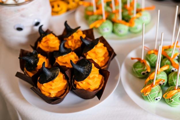 Petits gâteaux à la crème d'orange et de jolis chapeaux noirs sur la barre chocolatée pour la fête de halloween Photo Premium