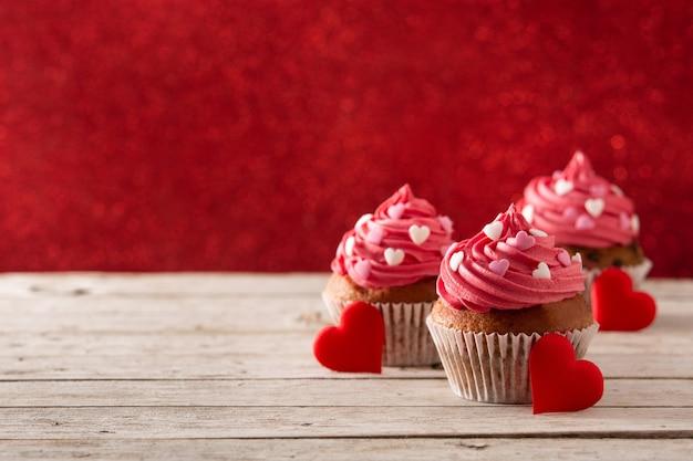 Petits Gâteaux Décorés De Coeurs De Sucre Pour La Saint-valentin Sur Table En Bois Et Fond Rouge Photo Premium