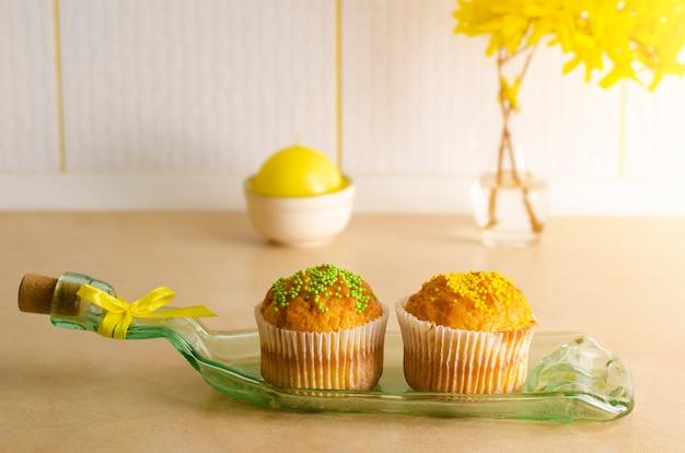 Petits gâteaux décorés avec des pépites sur une assiette faite à partir de bouteille sur une table de kithchen Photo Premium