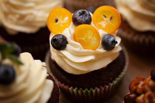 Petits gâteaux délicieux avec des baies sur une table en bois se bouchent Photo Premium