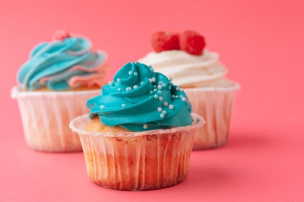 Petits gâteaux délicieux sur fond rose se bouchent Photo Premium